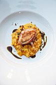 Pumpkin curry risotto with quail lemongrass skewer