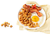 American breakfast with hashbrowns, bacon, pork, meat, tomatoes, and eggs sunny side up
