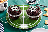Chocolate muffins with a football decoration on a plate in the colors of a football field