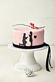 Pink wedding cake with black paper cut out decorations