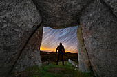 Man looking at a starry sky viewed from a dolmen, Portugal