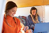 Young women friends using laptop in camper van