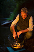 Man cooking freshly caught fish at dark riverbank