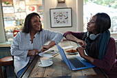 Mother and daughter elbow bumping at cafe table