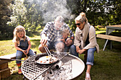 Happy family cooking breakfast on campsite grill
