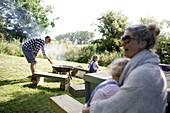 Family enjoying barbecue in sunny backyard