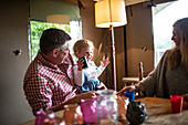 Happy father holding daughter at cabin table