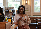 Woman with smartphone enjoying white wine in bar