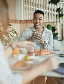 Businesswomen talking in breakfast meeting in office