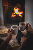 Mother and daughter enjoying hot cocoa by fireplace