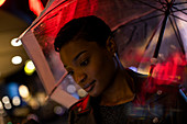 Young woman under umbrella with neon lights at night