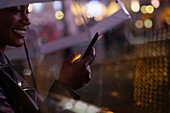 Young woman with smartphone under an umbrella at night