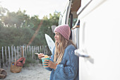 Young woman eating instant noodles outside camper van