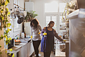 Mother and daughter in rubber gloves cleaning kitchen
