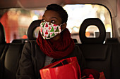Young woman in Christmas face mask in backseat of taxi