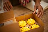 Woman reaching for lemon yellow cupcakes in bakery box