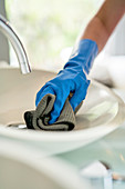Hotel maid in gloves cleaning hotel room bathroom sink