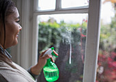 Woman cleaning windows with glass cleaner spray bottle