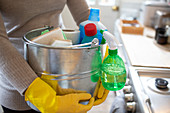 Woman in rubber gloves with cleaning supplies