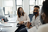 Business people in face masks talking in office meeting