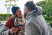 Affectionate romantic couple drinking red wine on patio