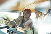 Young women friends using smartphone inside camper van
