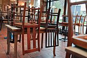 Wooden chairs upside down on tables in empty restaurant