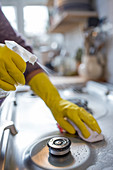 Woman in rubber gloves spray cleaning stovetop