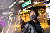 Young woman in studded face mask on city street at night