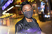 Young woman in sparkly mask in city with lights at night