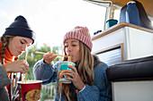 Young women friends eating instant noodles in camper van