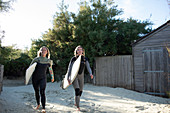 Young female surfers with surfboards on sunny beach path