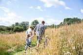 Family holding hands walking in rural field