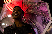 Smiling young woman under umbrella and neon sign at night