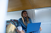 Carefree young woman with laptop and coffee in camper van