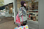 Young woman in face mask with shopping bags at storefront