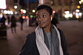 Young woman with earbud headphones on city street at night