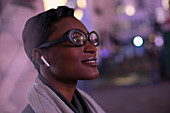 Young woman in eyeglasses on city street at night