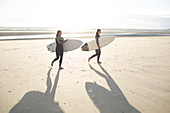 Young female surfers with surfboards on sunny summer beach