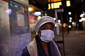 Young woman in face mask on city sidewalk at night