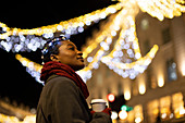 Young woman with coffee in city at night