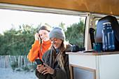 Young women friends using smartphone in camper van doorway