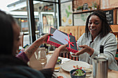 Daughter giving mother birthday gift at lunch in restaurant