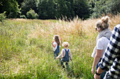 Parents following cute daughters in sunny rural summer field