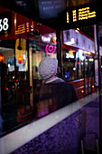 Young woman in hat waiting for city bus at night, london, uk