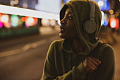 Young woman in hoody with headphones on city street at night