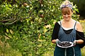Happy woman harvesting fresh blackberries in garden