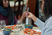 Mother and daughter holding hands over pizza and salad lunch