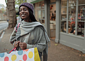 Happy young woman with shopping bag on sidewalk outside shop