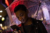Close-up young woman with umbrella using smartphone at night